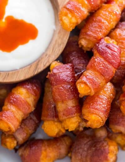 Bacon wrapped tater tots on a plate with a bowl of dip