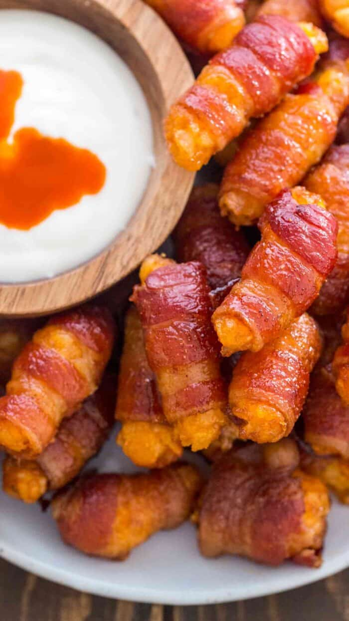 Bacon Wrapped Tater Tots piled on a plate with a creamy dipping sauce on the side