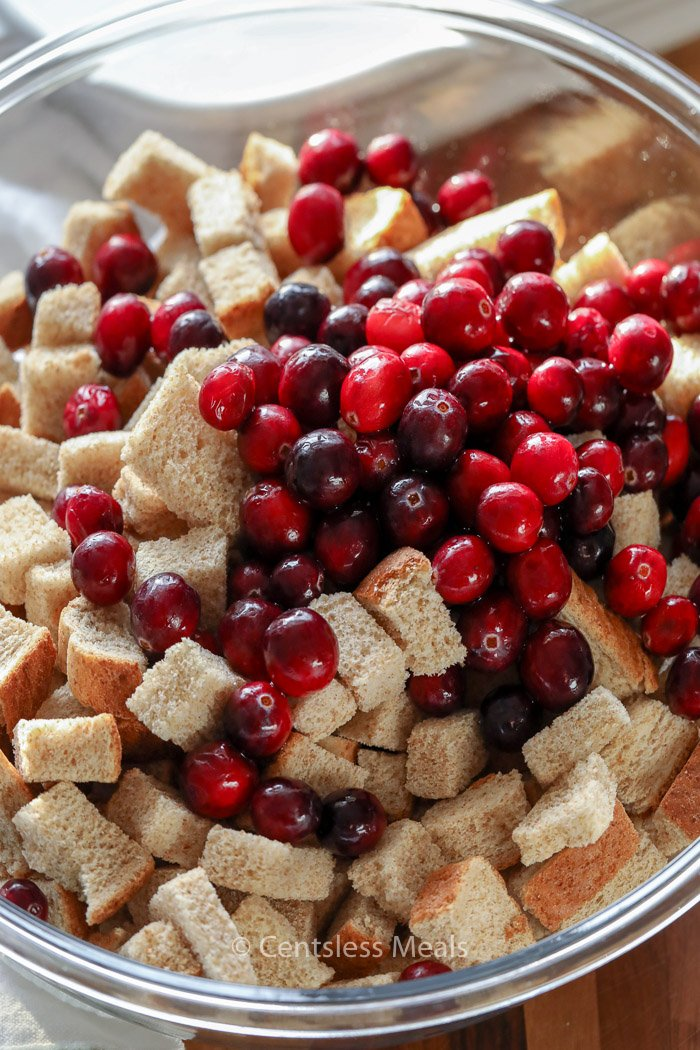 Dried bread cubes and fresh cranberries in a clear mixing bowl for bread pudding.