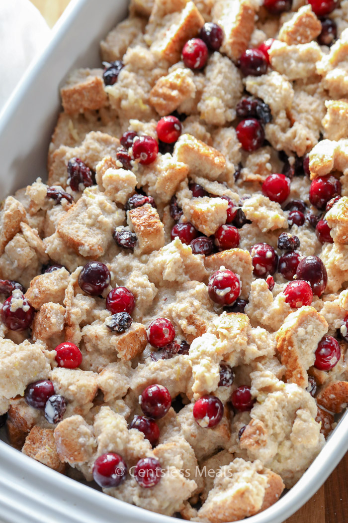 Cranberry bread pudding in a white baking dish with fresh cranberries.
