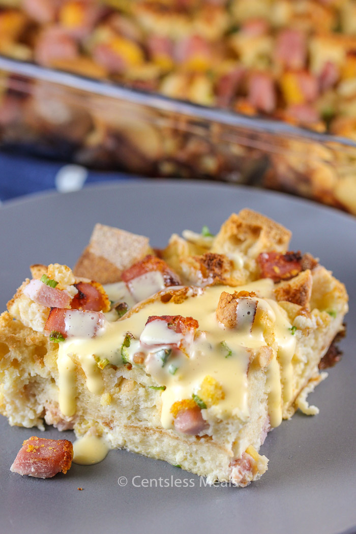 Eggs benedict casserole with creamy hollandaise sauce on a grey plate.