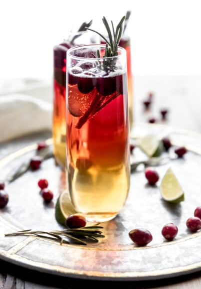 Cranberry Champagne cocktail being served on a round silver tray garnished with fresh cranberries, lime wedges, and rosemary sprigs.