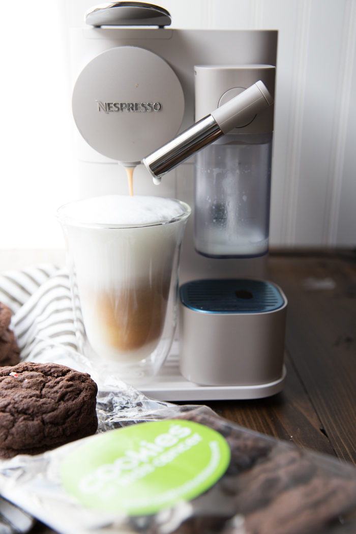 Peppermint mocha being brewed with an espresso machine with cookies on the side