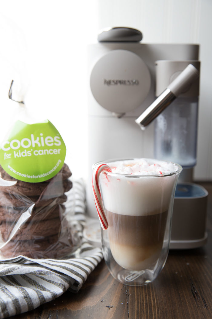 Peppermint mocha in a clear mug with cookies and an espresso machine