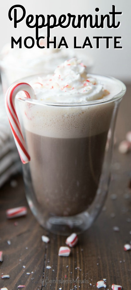 A peppermint mocha latte in a clear mug garnished with a candy cane