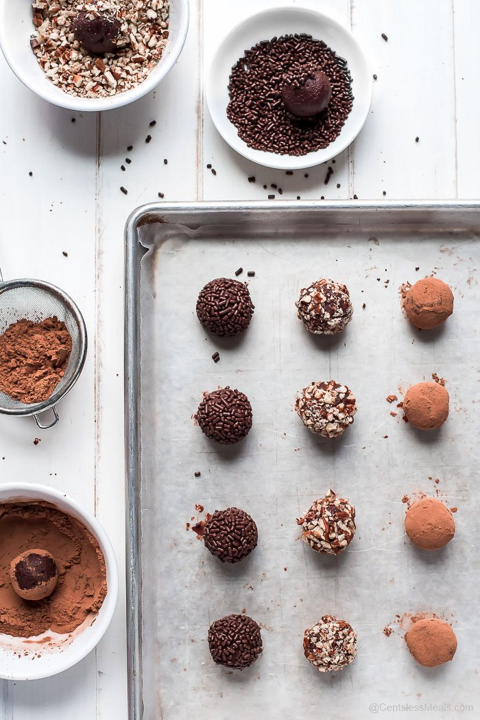 Chocolate truffles assembled on a cookie sheet with bowls of nuts, sprinkles and cocoa for dipping