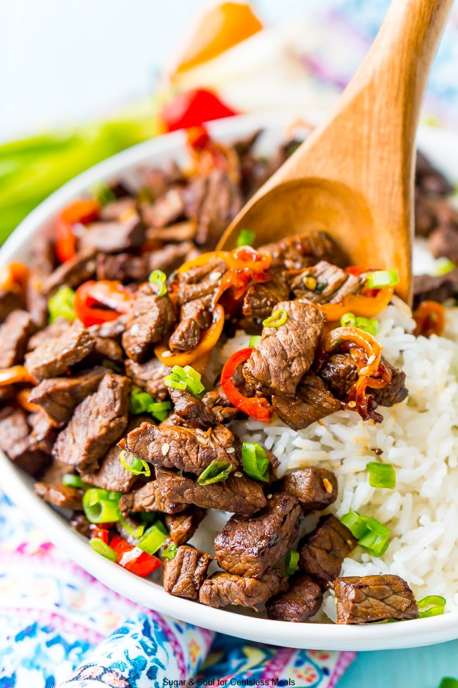 White bowl full of pepper steak with rice and a wooden spoon
