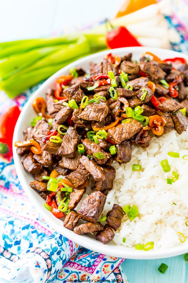 Pepper steak in a white bowl with rice garnished with green onions and sesame seeds