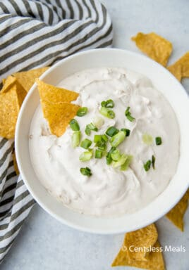 Onion dip in a white bowl topped with green onions and tortilla chips on the side