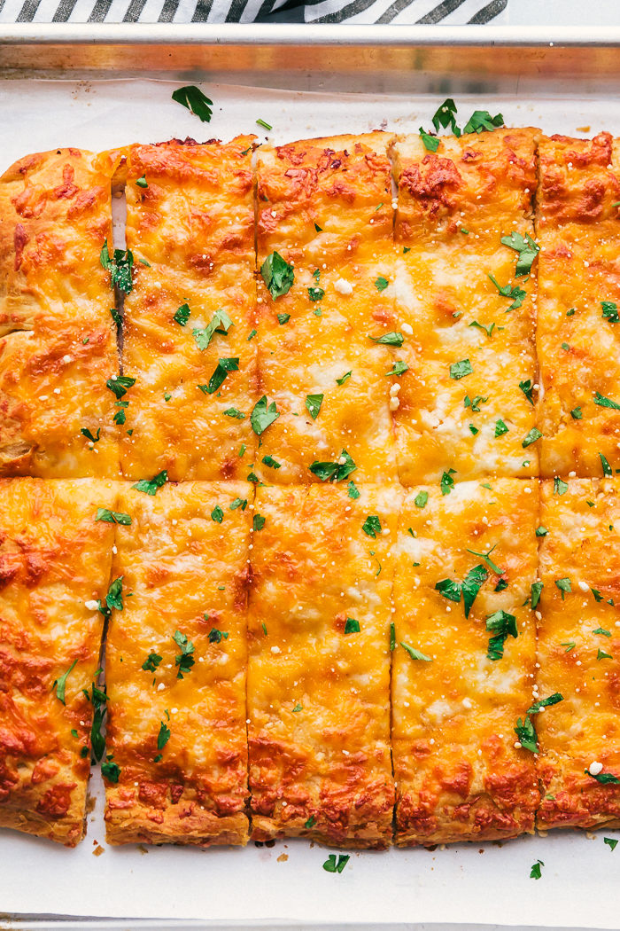 Cheesy breadsticks on a sheet pan garnished with parsley