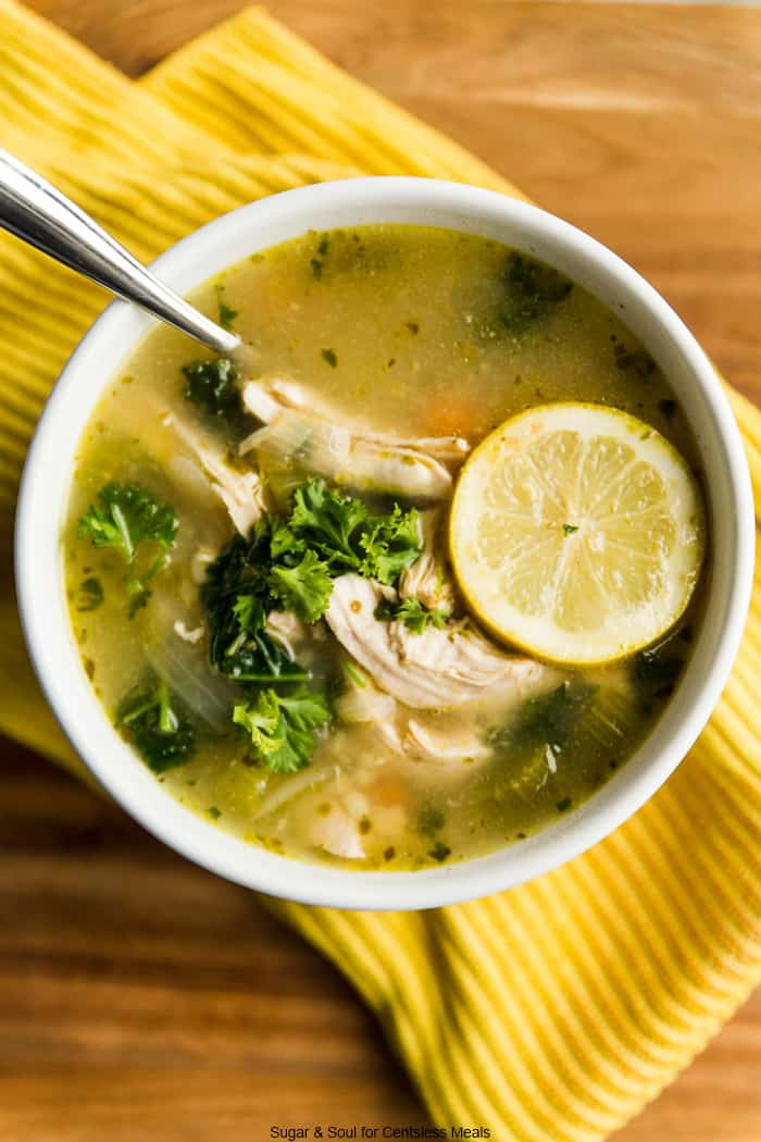 Chicken kale soup in a white bowl garnished with parsley and a lemon slice