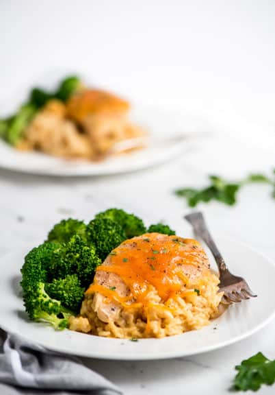 Crock-Pot Crock-Pot cheesy chicken rice on a white plate with broccoli and a fork