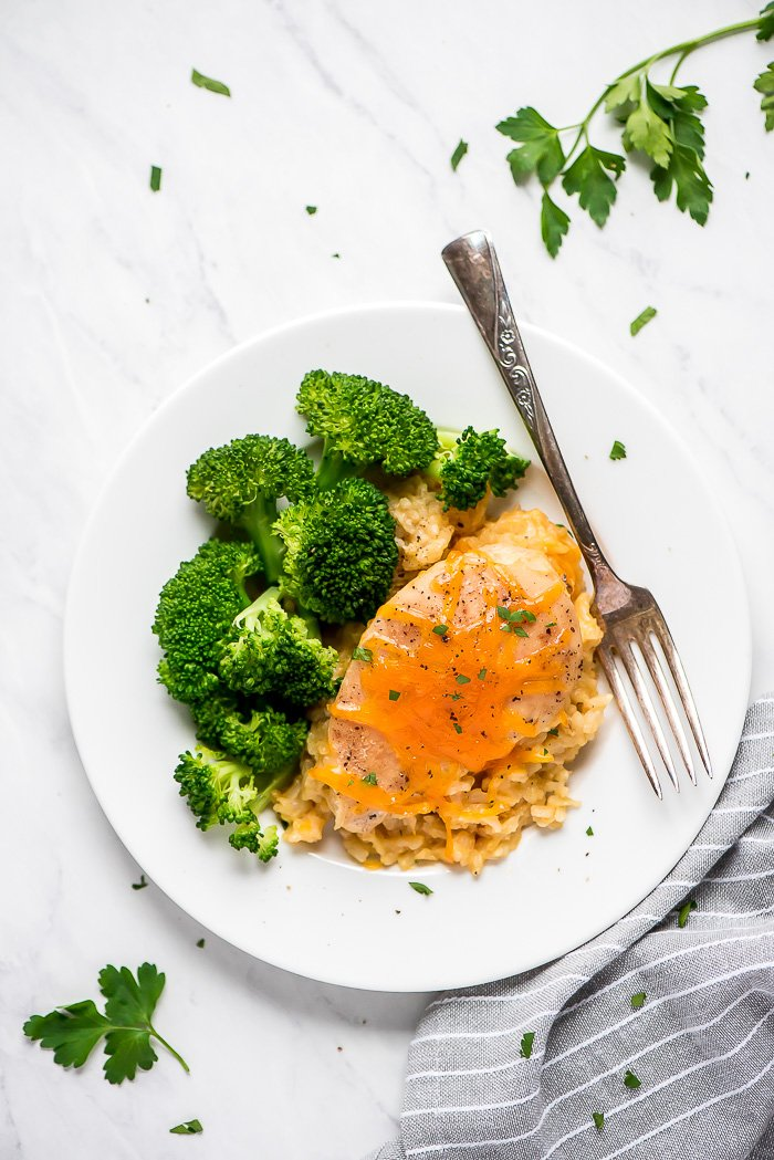 Top view of Slow Cooker Cheesy Chicken and Rice on a white plate with a side of broccoli.