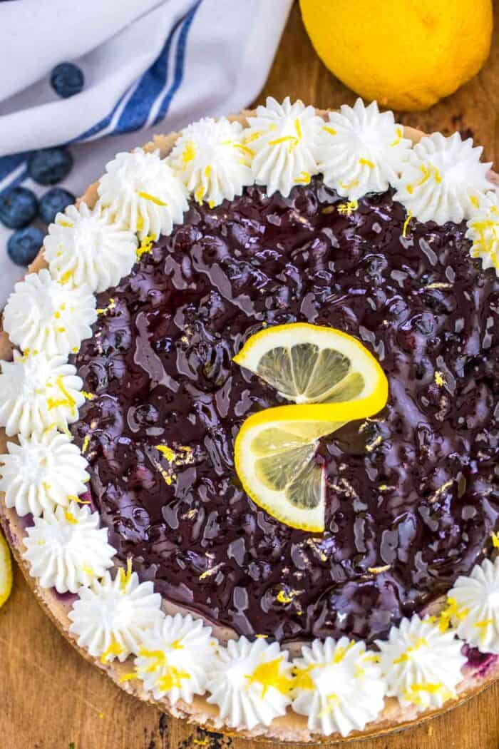A top view of Blueberry Cheesecake garnished with whipped cream around the edges and a lemon swirl and lemon zest for garnish