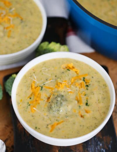 Broccoli Soup in white bowls garnished with shredded cheddar