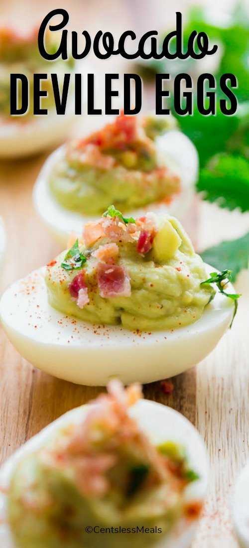 Avocado deviled eggs on a wooden board with writing