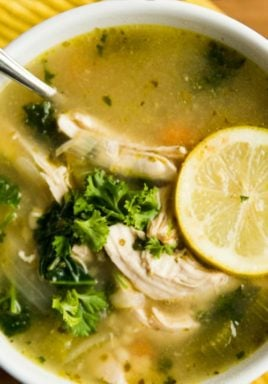 Chicken kale soup in a white bowl with writing