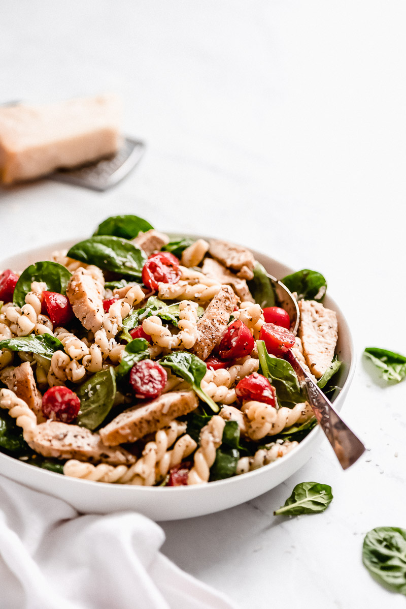 Closeup side view of Spinach & Tomato Chicken Pasta Salad in a serving bowl,