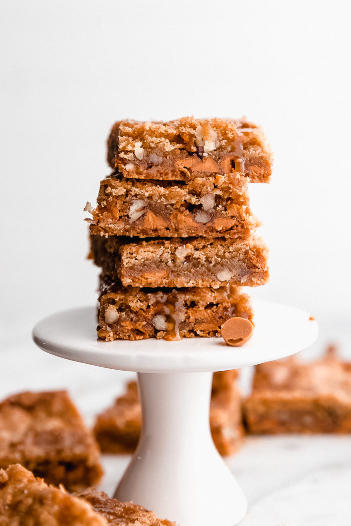Butterscotch blondies stacked on top of each other on a round white dessert pedestal topped with butterscotch topping on a white back ground