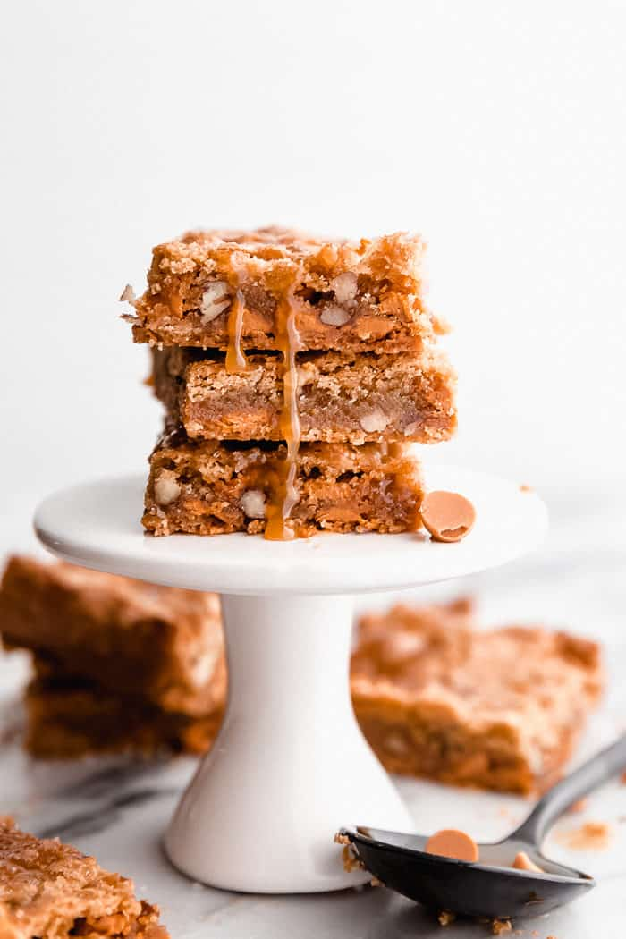 Three Butterscotch Blondies stacked on top of each other on a white pedestal dessert holder with butterscotch topping dripping down the blondies on a white background