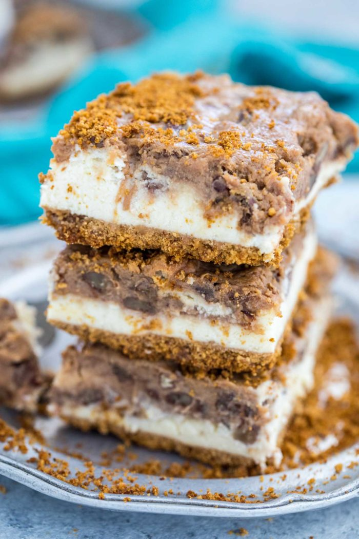 Three Pecan Pie Cheesecake Bars are stacked up together on a silver plate with a teal colored napkin in the background.