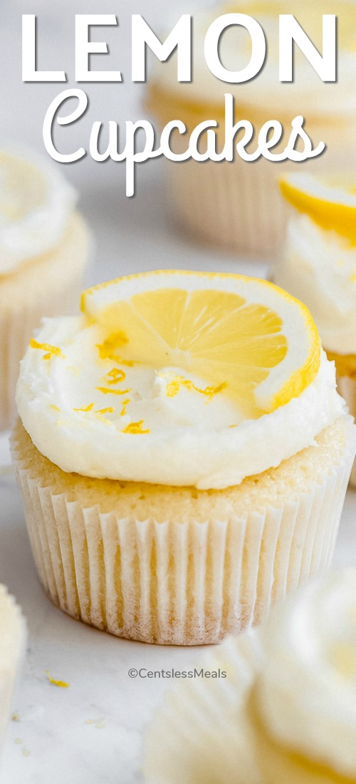 A lemon cupcake frosted and decorated with a lemon slice and lemon zest on top