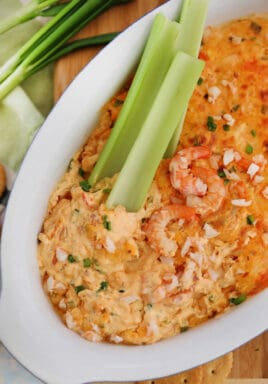 Shrimp dip in a white bowl with celery sticks and shrimp on top