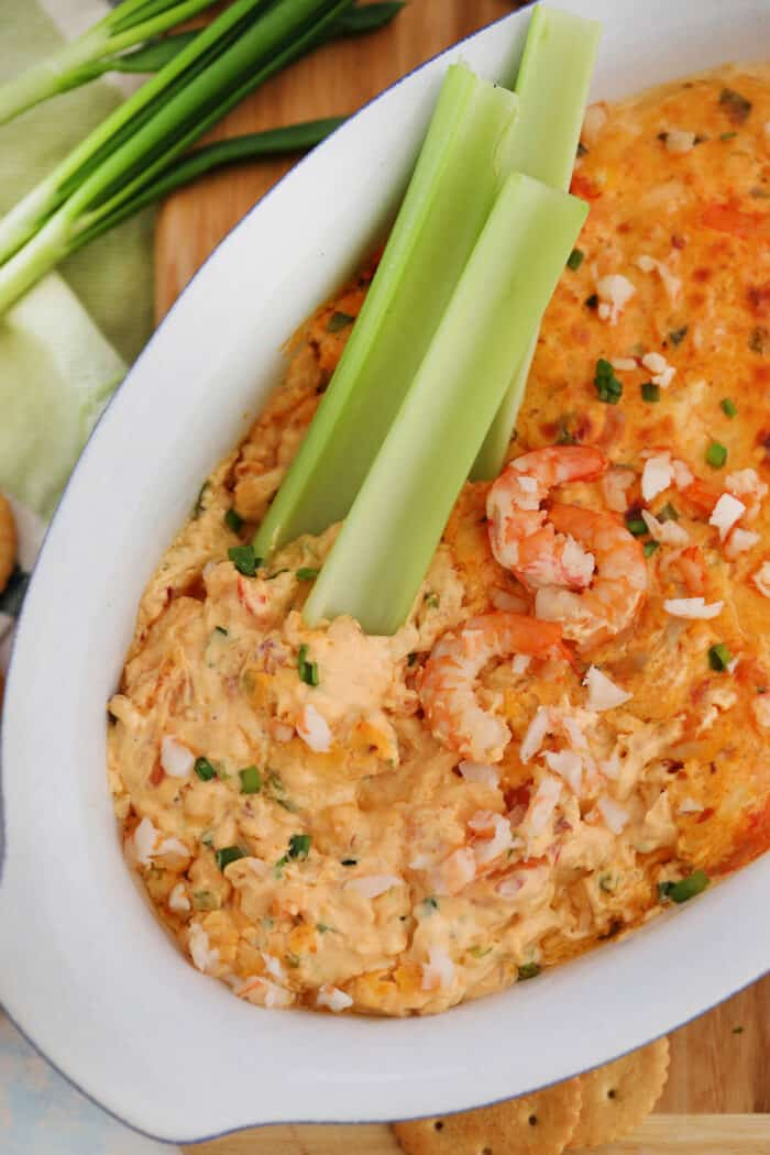 Shrimp Dip in a white serving dish with three stalks of celery in it.