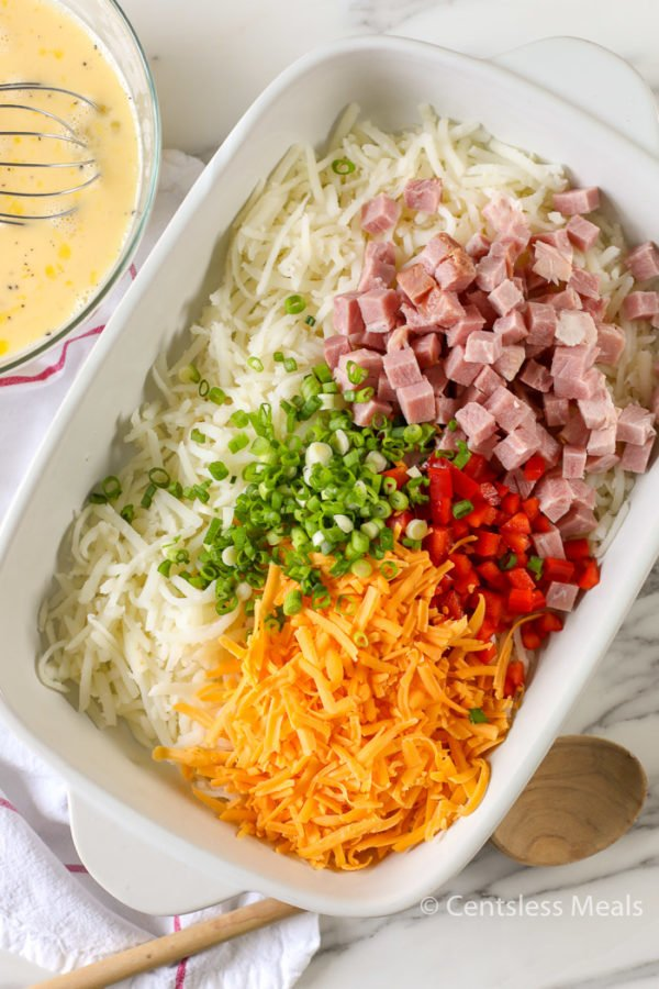 Ingredients for Simply Potatoes hash brown breakfast casserole in a white casserole dish
