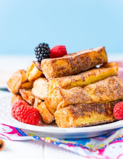 French toast sticks topped with berries on a white plate