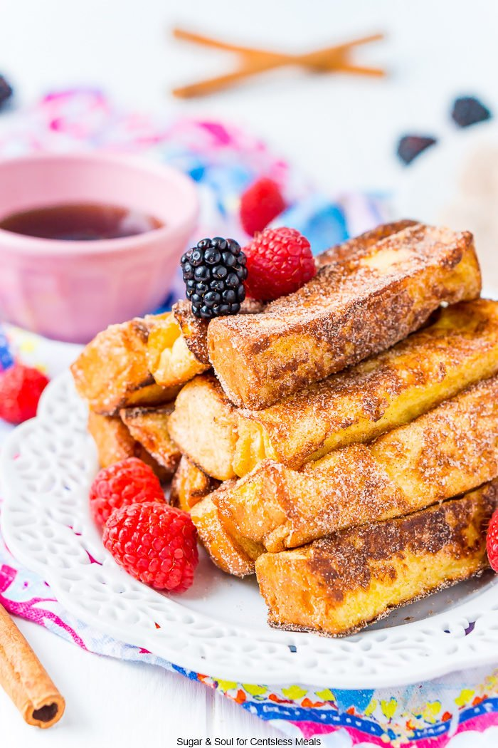 French toast sticks on a white plate with raspberries and blackberries