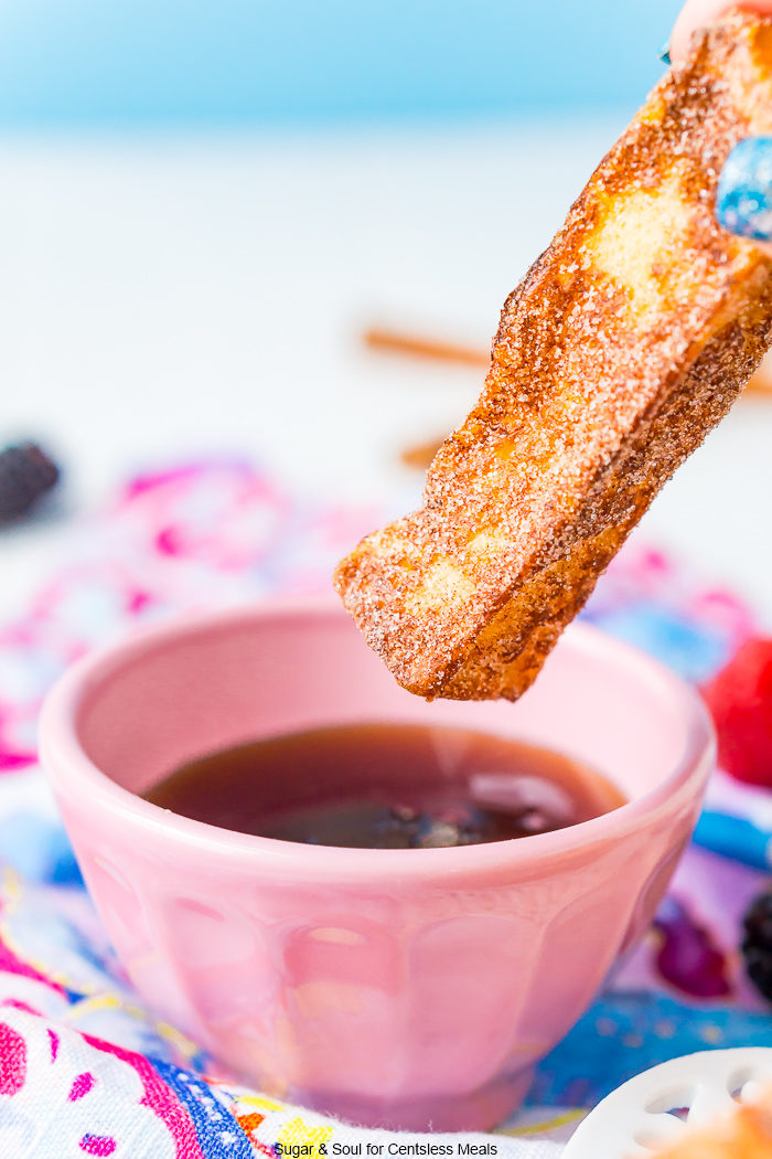 French toast stick with a bowl of syrup