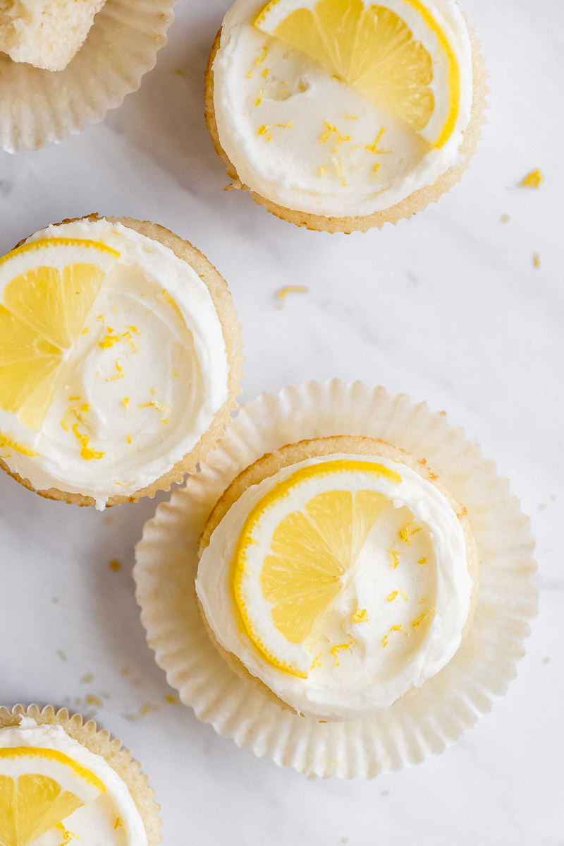 Close up of the top of Lemon Cupcakes with frosting, lemon zest, and half lemon slices.