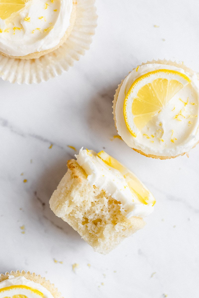 A few Lemon Cupcakes frosted with lemon buttercream and one with a bite taken out, showing the fluffy texture.