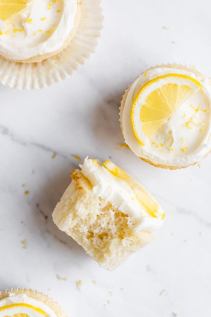 A bite taken out of a lemon cupcake