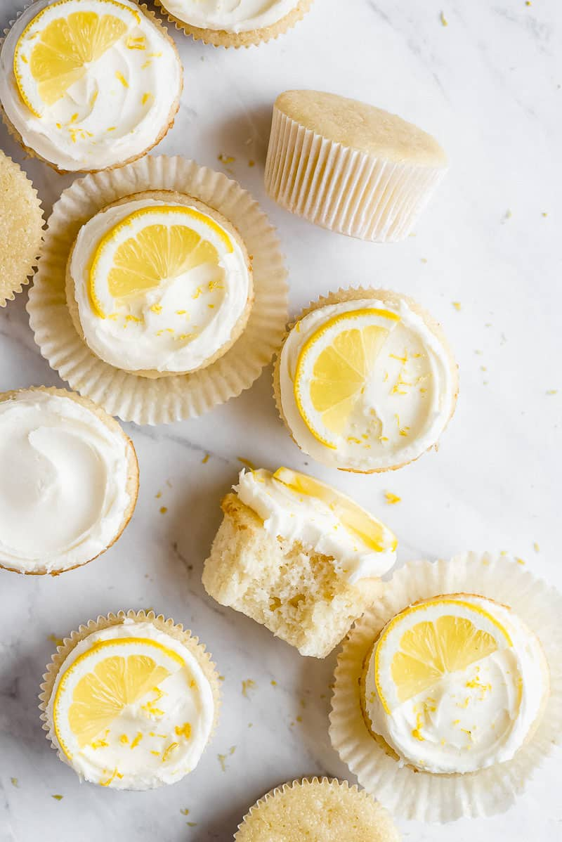 Lemon cupcakes scattered on a white marble countertop