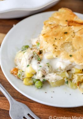 Chicken pot pie on a white plate with a fork and parsley