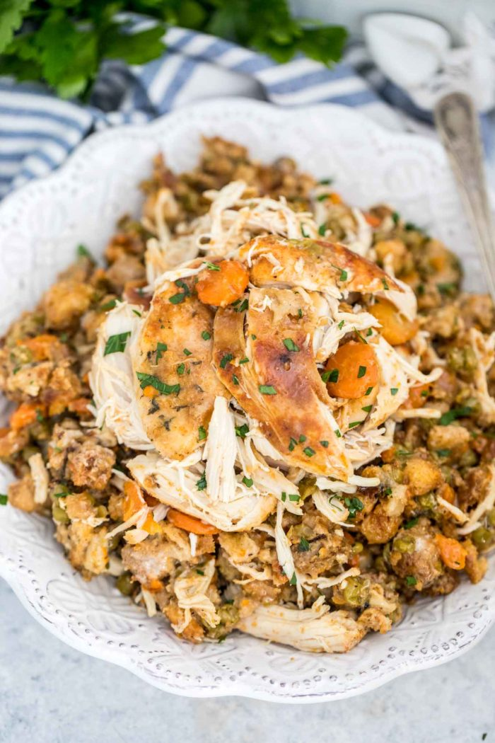 Crockpot Chicken and Stuffing on a plate with a fork garnished with parsley