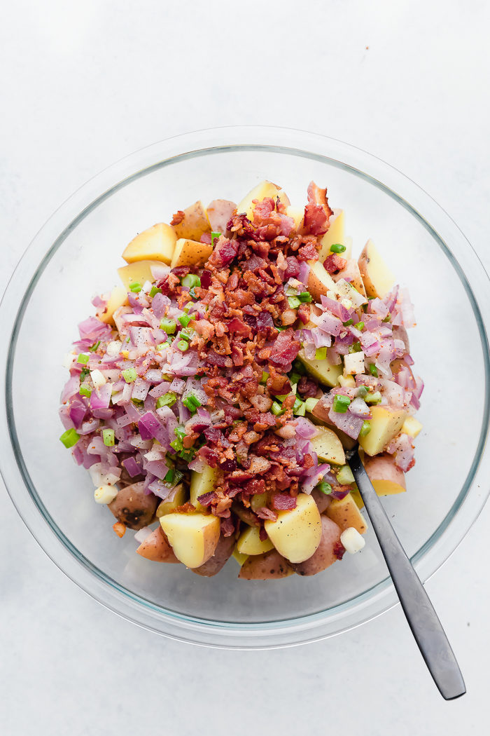 All the ingredients for German Potato Salad assembled in a clear bowl and ready to be tossed.