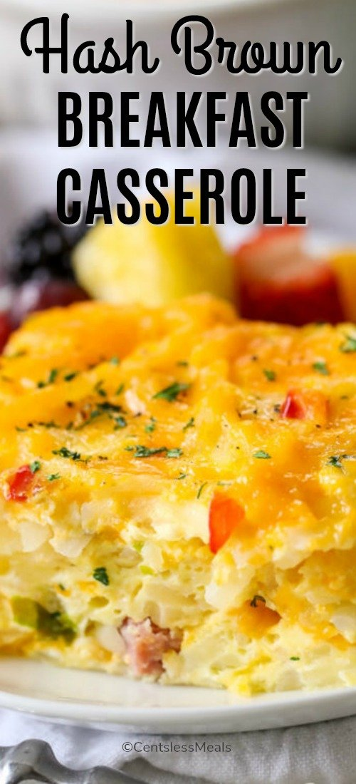 A close up photo of Hash Brown Breakfast Casserole on a white plate with fresh fruit in the background.