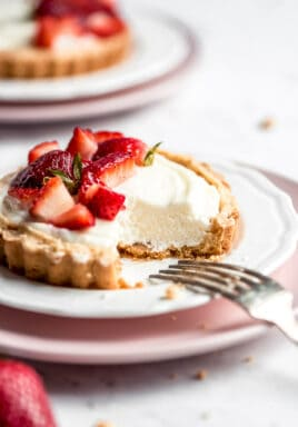 Strawberry mini tarts on plates with a fork