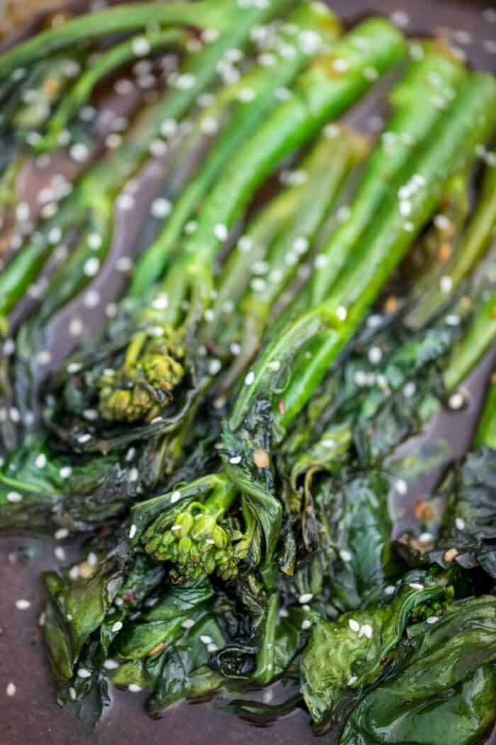 A close up of cooked Chinese Broccoli drenched in a garlicky asian sauce