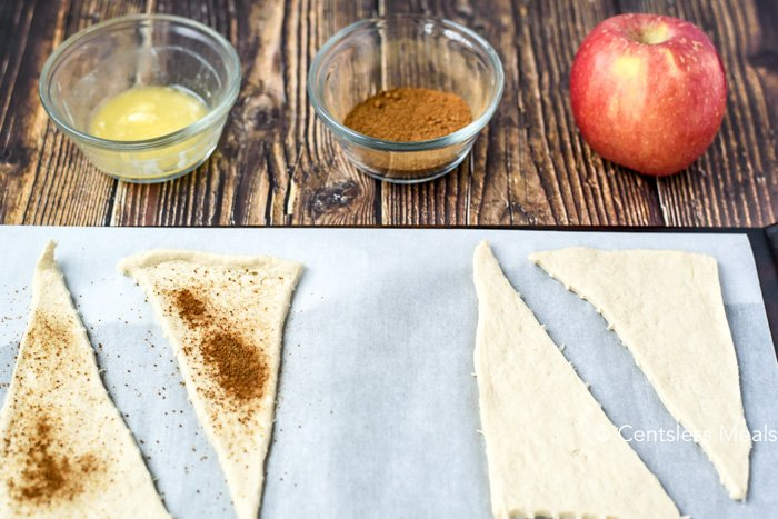 Raw dough for cinnamon apple crescents on parchment paper with butter cinnamon and an apple