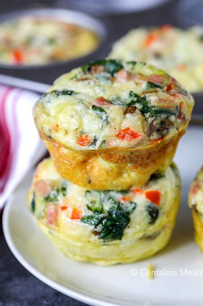 Two baked egg muffins stacked on a white plate.