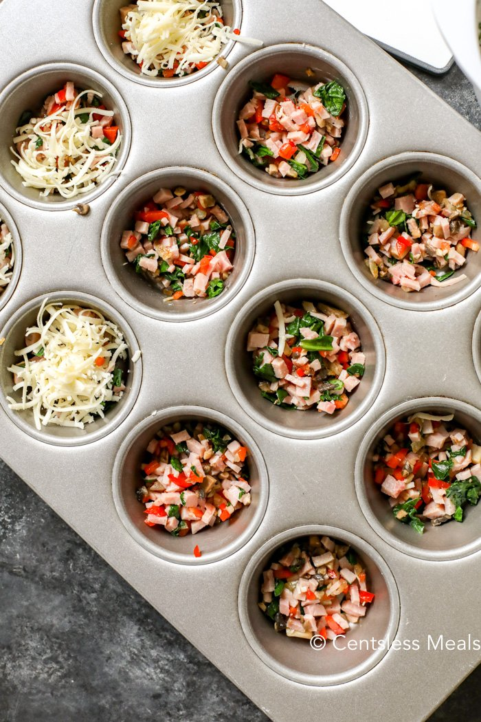 A muffin tin with diced ham and veggies in each cup, a few topped with mozzarella cheese before the egg mixture is poured on top.