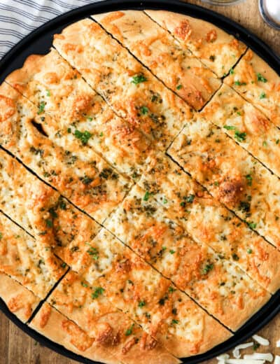 Pizza dough breadsticks on a pizza sheet with parsley