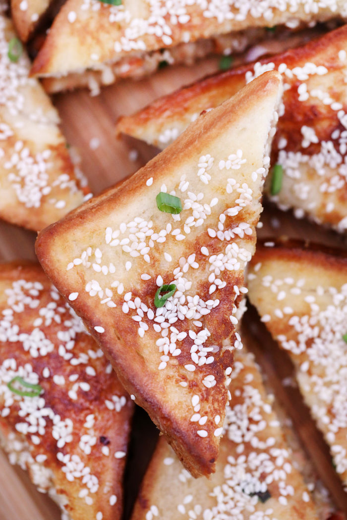 Triangles of Shrimp Toast piled together with sesame seeds and greed onions for garnish