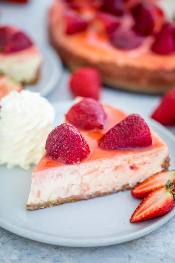 Strawberry cheesecake on a plate with strawberries and whipped cream