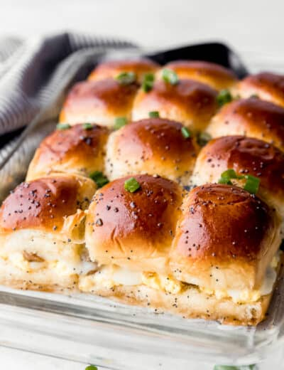 Breakfast sandwiches in a clear casserole dish with green onions on top