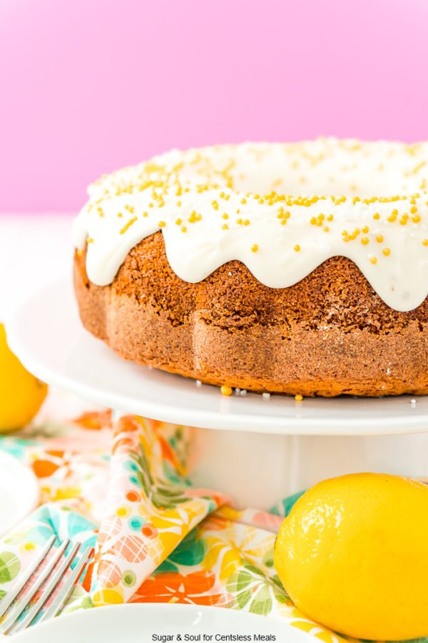 Citrus flavored bundt cake on a white cake stand with icing and sprinkles.
